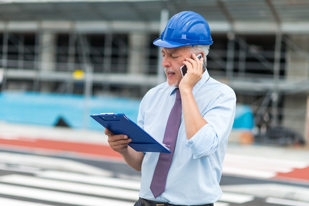 Architekt rozmawia przez telefon przed placem budowy Premium Zdjęcia