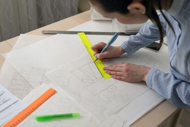 Architekt-student rysuje kształty geometryczne, praktykę projektową Premium Zdjęcia