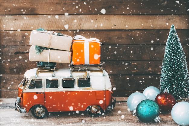 Archiwalne pocztówki w tle wesołych świąt miniaturowe zabytkowe auto przewożące prezenty (pudełko) na dachu i choince w śnieżną zimę. Premium Zdjęcia