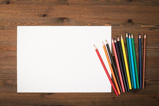 Arkusz To Czysto Białe I Kolorowe Kredki Do Rysowania Na Drewnianym Tle Z Miejscem Do Skopiowania. Makieta, Makieta, Układ. Premium Zdjęcia