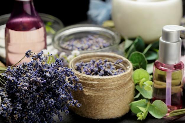 Aromatyczna Kompozycja Lawendy, Ziół, Kosmetyków I Soli Na Ciemnym Blacie Premium Zdjęcia