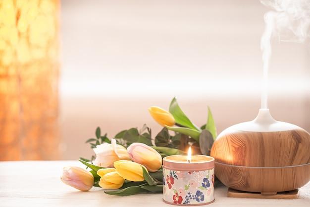 Aromatyczny Dyfuzor Olejny Na Stole Na Blacie Rozmazany Z Pięknym Wiosennym Bukietem Tulipanów I Płonących świec. Darmowe Zdjęcia