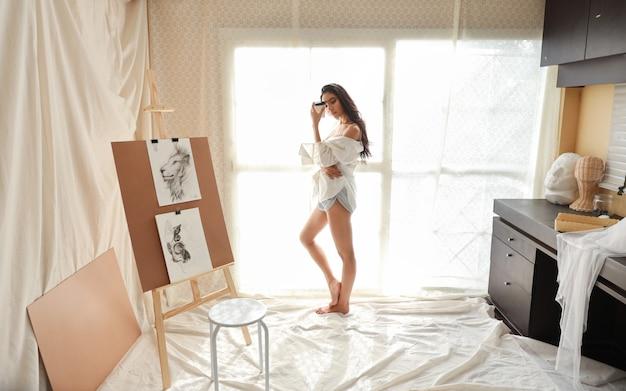 Artysta azjatyckich kobiet w pełnej długości w białej koszuli picia kawy podczas rysowania ołówkiem (koncepcja stylu życia kobiety) Premium Zdjęcia