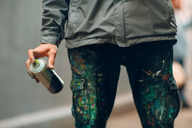 Artysta Graffiti W Ubraniach Poplamionych Farbą W Sprayu Może W Dłoni Premium Zdjęcia