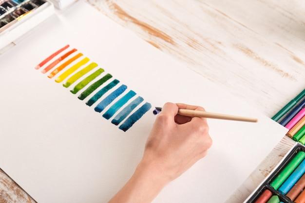 Artysta Malujący Kolorowe Paski Pędzlem Na Białym Papierze Darmowe Zdjęcia
