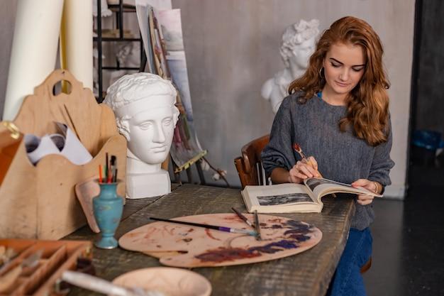 Artysta maluje na sztaludze w studio. kobieta malarz widziany z boku. Premium Zdjęcia