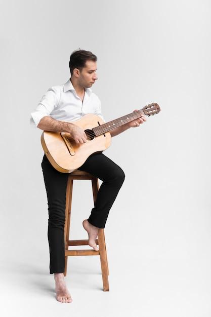 Artysta Mężczyzna W Studio Gra Na Gitarze Klasycznej Darmowe Zdjęcia