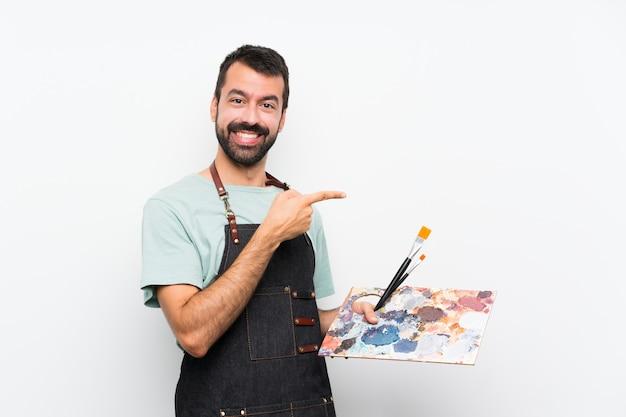 Artysta młody człowiek trzyma paletę palcem wskazującym na bok Premium Zdjęcia
