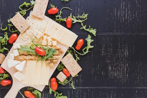 Arugula opuszcza z pomidorami, serem, breadsticks i chrupiącym chlebem na czarnym textured tle Darmowe Zdjęcia