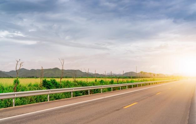 Asfaltowa Droga Obok Zielonej Trawy Pola I Góry Z światłem Słonecznym. Długodystansowa Podróż Z Niebieskim Niebem I Białą Chmurą. Droga Asfaltowa Wiejska. Koncepcja Podróży Podróż Samochodem. Premium Zdjęcia