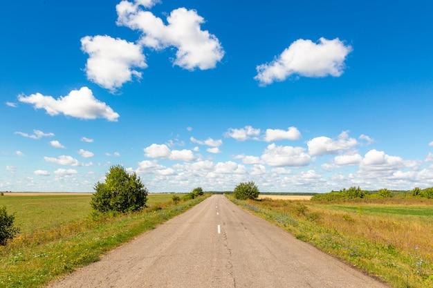 Asfaltowa Droga Przez Zielonego Pola I Chmur Na Niebieskim Niebie Premium Zdjęcia