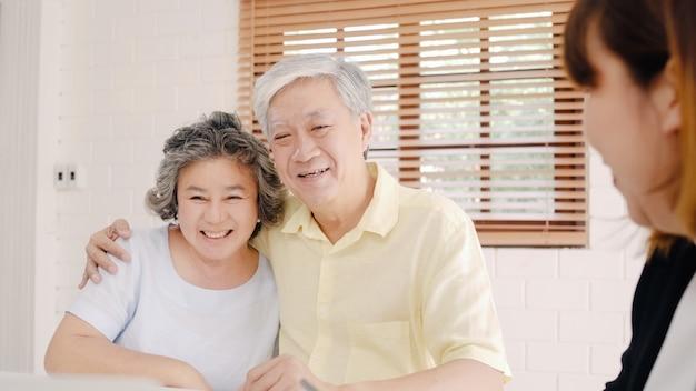 Asia smart female agent oferuje ubezpieczenie zdrowotne dla starszych par według dokumentów, tabletów i laptopów. Darmowe Zdjęcia