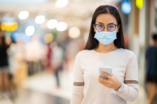 Asian Kobieta Ma Na Sobie Maskę I Trzymaj Telefon Komórkowy Zakupy W Sklepie W Trakcie Premium Zdjęcia
