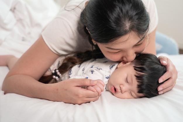 Asian Matka Całuje I Dotyka Dziecko, Które śpi Delikatnie Na łóżku Z Miłością Premium Zdjęcia