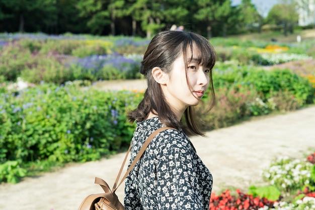 Asian Młoda Kobieta Na Spacer W Kwiatowym Polu Premium Zdjęcia