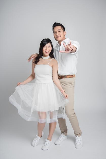 Asian para zakochanych w swobodnej sukni ślubnej pokazując, że kocham cię gest Premium Zdjęcia