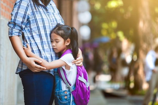 Asian Uczeń Dziewczyna Z Plecakiem Przytulanie Matki Ze Smutkiem Przed Pójściem Do Klasy W Szkole. Premium Zdjęcia