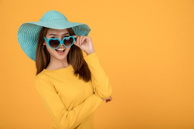 Asian woman dress up concept wakacje z żółtą koszulą okulary i kapelusze są niebieskie i sprawiają, że twarze są bardzo szczęśliwe. Premium Zdjęcia