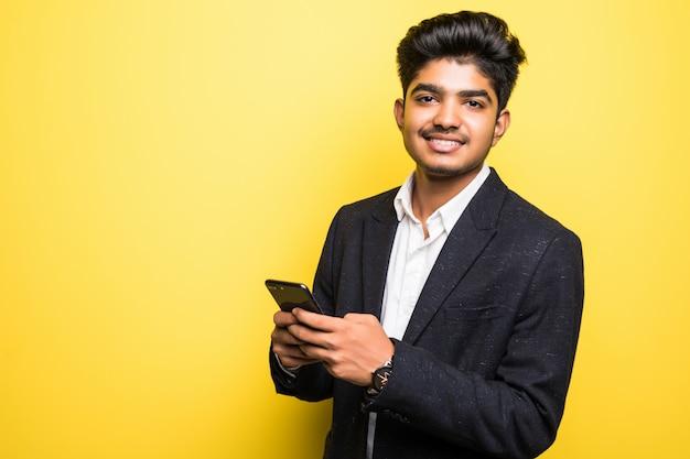 Asianindian Biznesowego Mężczyzna Przystojny Mężczyzna Używa Mądrze Telefon Na Kolor żółty ścianie Darmowe Zdjęcia
