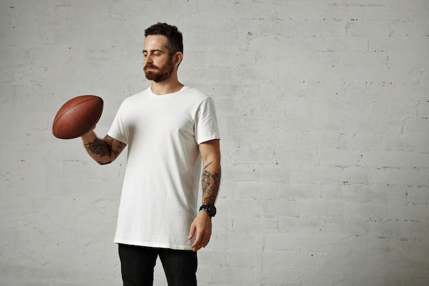 Atletyczny Wytatuowany Hipster W Białej Bawełnianej Koszulce Bez Etykiety, Czarnych Dżinsach I Dużym Czarnym Zegarku Ze Starą Brązową Piłką Do Rugby Darmowe Zdjęcia