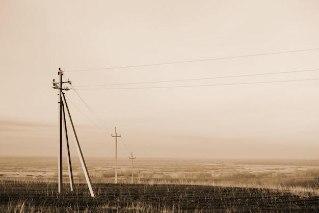 Atmosferyczny krajobraz z liniami energetycznymi w polu pod niebem w odcieniach sepii. tło wizerunek elektryczni filary z copyspace. przewody wysokiego napięcia nad ziemią. przemysł elektryczny w trybie monochromatycznym. Premium Zdjęcia