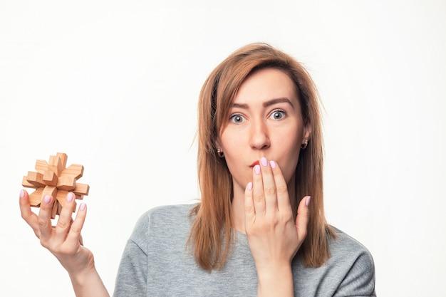 Atrakcyjna 24-letnia Kobieta Biznesu Patrząc Zmieszany Z Drewnianą łamigłówką. Darmowe Zdjęcia