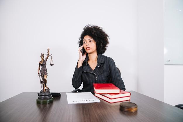 Atrakcyjna amerykanin afrykańskiego pochodzenia kobieta opowiada na telefonie komórkowym przy stołem w biurze Darmowe Zdjęcia