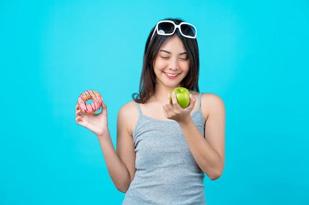 Atrakcyjna Azjatycka Młoda Kobieta Trzyma I Wybiera Między Dyskiem Pączki Lub Zielona Jabłczana Owoc Na Odosobnionej Błękitnej Kolor ścianie Premium Zdjęcia