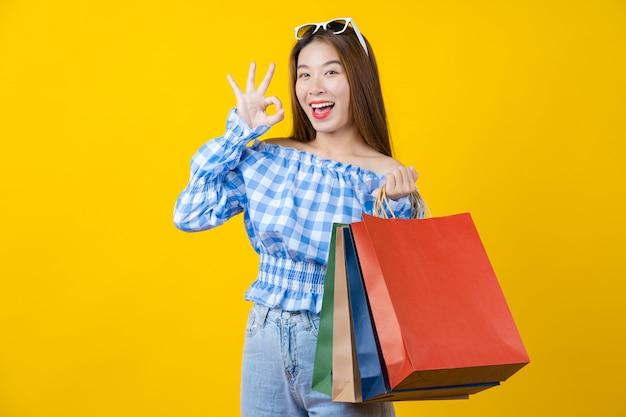 Atrakcyjna Azjatycka Uśmiechnięta Młoda Kobieta Niesie Zakupy Coloful Torbę I Gestykuluje Ok Znaka Zgoda Na Aisolated Kolor żółty ścianie Premium Zdjęcia
