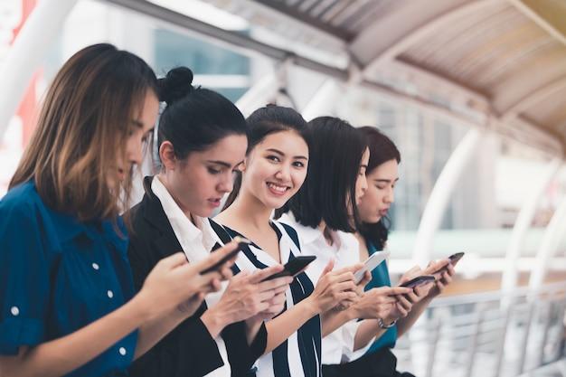 Atrakcyjna azjatykcia bizneswoman drużyna bawić się smartphone plenerowego miasto Premium Zdjęcia