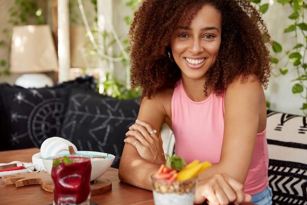 Atrakcyjna Ciemnoskóra Afroamerykanka Ubrana W Różową Koszulkę, Siedzi Ze Skrzyżowanymi Dłońmi Przy Stole W Kawiarni, Otoczona Koktajlami I Słodkim Deserem, Ma Zadowoloną Minę, Dobrze Wypoczywa. Darmowe Zdjęcia