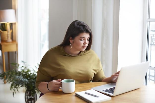 Atrakcyjna Ciemnowłosa Pulchna Freelancerka Siedząca W ładnej Kawiarni, Sprawdzająca Pocztę E-mail I Popijająca Poranną Kawę, Używając Zwykłego Laptopa I Trzymając Kubek, Patrząc Na Ekran, Czytająca Wiadomości Ze świata Darmowe Zdjęcia