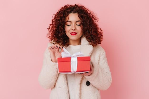 Atrakcyjna Dama Trzyma Czerwone Pudełko Z Białą Wstążką Na Różowej Przestrzeni. Migawka Kręconej Dziewczyny W Stroju Z Lekkiej Wełny. Darmowe Zdjęcia