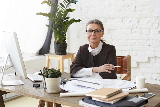 Atrakcyjna Dojrzała Kobieta Architekt W Okularach, Ciesząca Się Procesem Pracy W Jasnym, Przestronnym Biurze, Siedząca Przed Zwykłym Komputerem, Trzymająca Ołówek, Badająca Rysunki I Specyfikacje Na Biurku Darmowe Zdjęcia