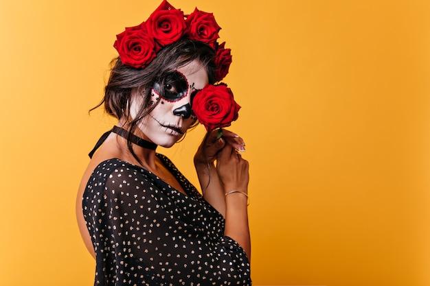 Atrakcyjna Dojrzała Kobieta W Halloweenowym Stroju Kocha Róże. Zbliżenie Portret Meksykańskiej Kobiety, Zamykając Oczy Z Czerwonym Kwiatem. Darmowe Zdjęcia