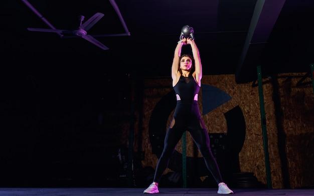 Atrakcyjna Dysponowana Kobiety Atleta Wykonuje Huśtawki Dzwonu Czajnika W Gym Premium Zdjęcia