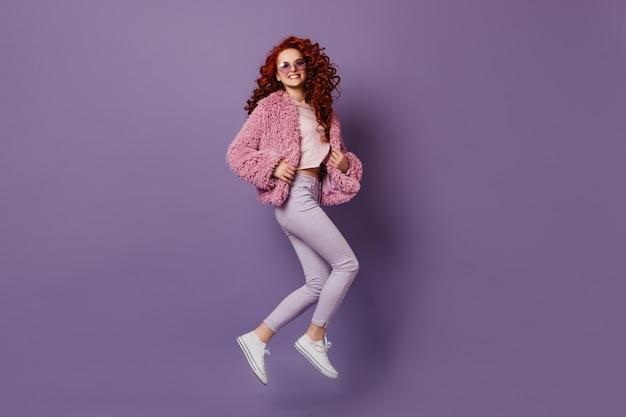 Atrakcyjna Dziewczyna W Stylowych Obcisłych Spodniach, Białej Koszulce I Różowym Płaszczu Skacze Na Liliowej Przestrzeni. Darmowe Zdjęcia