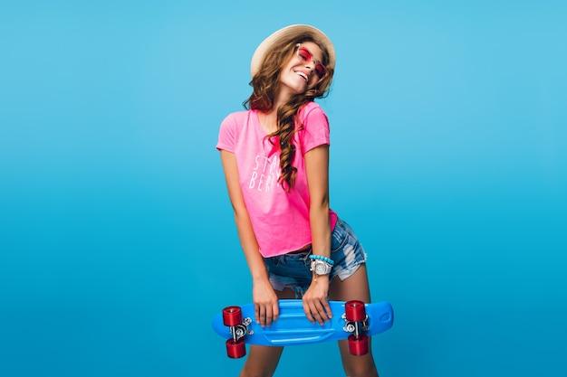 Atrakcyjna Dziewczyna Z Długimi Kręconymi Włosami W Kapeluszu, Pozowanie Na Niebieskim Tle W Studio. Nosi Szorty, Różową Koszulkę, Różowe Okulary Przeciwsłoneczne. Trzyma Niebieską Deskorolkę. Darmowe Zdjęcia