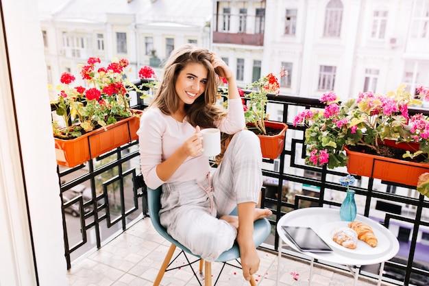 Atrakcyjna Dziewczyna Z Długimi Włosami W Piżamie Jedząc śniadanie Na Balkonie Rano W Mieście. Trzyma Filiżankę I Uśmiecha Się. Darmowe Zdjęcia
