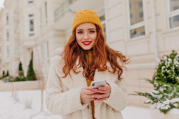 Atrakcyjna Kobieta Kaukaski W Dzianiny Kapelusz Trzymając Telefon. Zdjęcia Plenerowe Inspirowanej Rudej Dziewczynki W Białym Fartuchu Darmowe Zdjęcia