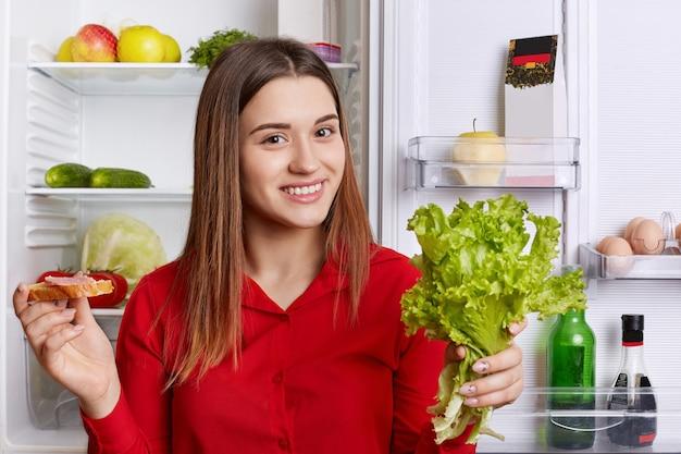 Atrakcyjna Kobieta Nosi Modną Czerwoną Bluzkę, Stoi Przy Otwartej Lodówce, Trzyma Sałatę I Kanapkę, Przygotowując Pyszny Obiad. Premium Zdjęcia