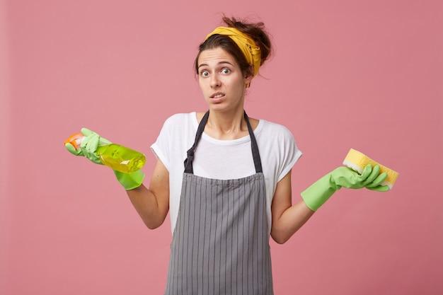 Atrakcyjna Kobieta O Europejskim Wyglądzie W Fartuchu, Wzruszająca Ramionami Z Zakłopotaniem, Trzymając Detergent I Gąbkę, Nie Wiedząc, Co Najpierw Wyczyścić. Pokojówka Ma Wątpliwości Darmowe Zdjęcia