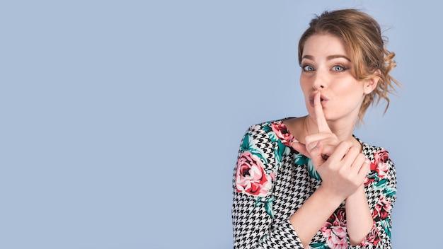 Atrakcyjna kobieta pokazano spokojny gest w eleganckiej sukni Darmowe Zdjęcia