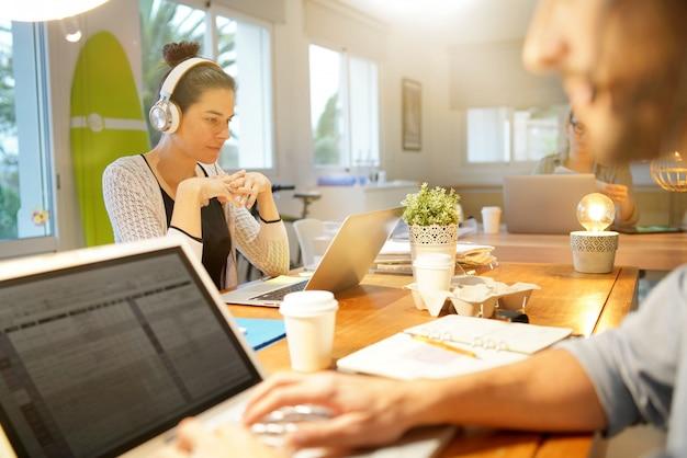 Atrakcyjna kobieta pracuje w co pracującej powierzchni biurowej Premium Zdjęcia