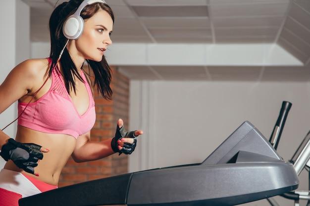 Atrakcyjna kobieta robi ćwiczenia cardio, bieganie na bieżniach na siłowni Premium Zdjęcia