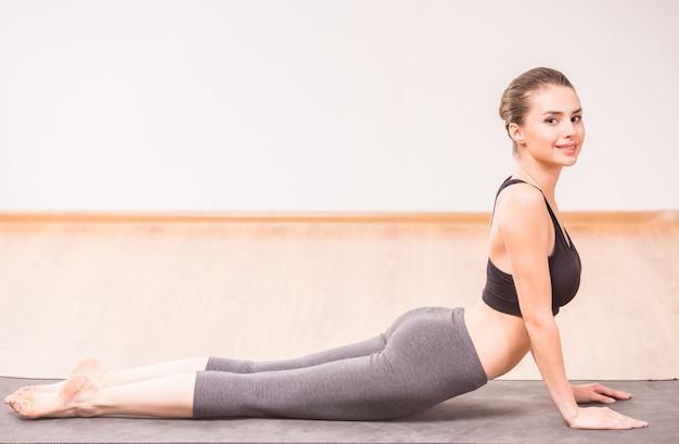 Atrakcyjna kobieta robi górę joga psiej pozyci na macie. Premium Zdjęcia