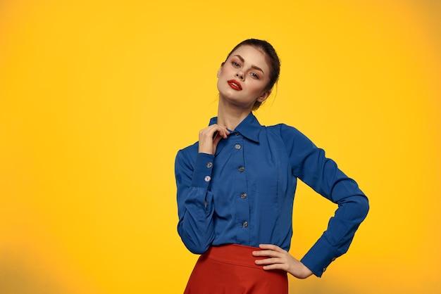 Atrakcyjna Kobieta W Niebieskiej Koszuli Gestykuluje Z Rękami I Czerwoną Spódnicą Na żółtym Tle Premium Zdjęcia