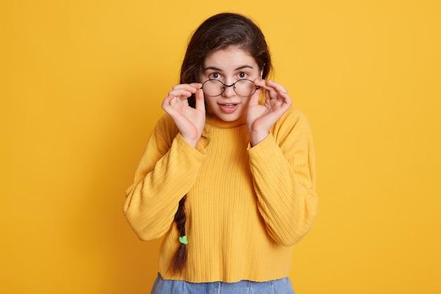 Atrakcyjna Kobieta W Nowych Okularach Trzymając Ręce Na Ramce, Pozowanie Na Białym Tle Nad żółtą ścianą Ze Zdumionym Wyrazem Twarzy, Ubrana W Swobodny Sweter. Premium Zdjęcia