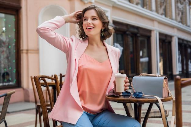 Atrakcyjna Kobieta W Romantycznym Nastroju, Uśmiechnięta Ze Szczęścia, Siedząca Przy Stole W Różowej Kurtce, Stylowa Odzież, Czekająca Na Chłopaka Na Randce W Kawiarni, Pijąca Cappuccino, Pełen Wyrazu Twarzy Darmowe Zdjęcia