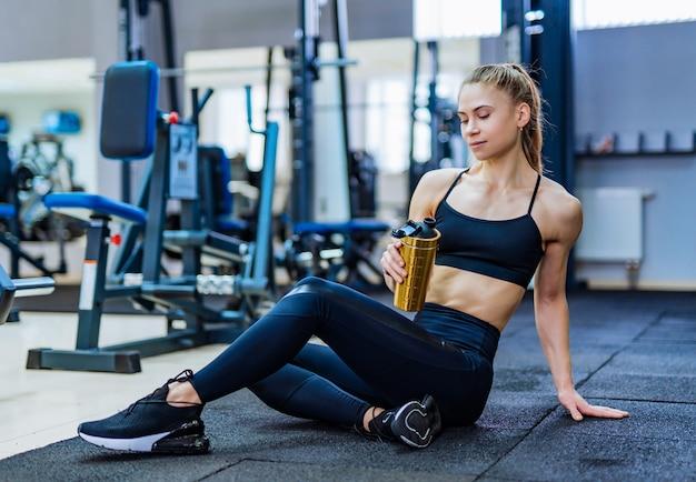 Atrakcyjna Kobieta W Sportowej Z Sportowym Bidonem W Ręku Spoczywa Na Podłodze Po Treningu W Siłowni. Premium Zdjęcia